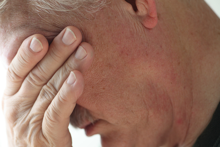 discouraged: Depressed older man averts his head, covering his eyes with a hand.