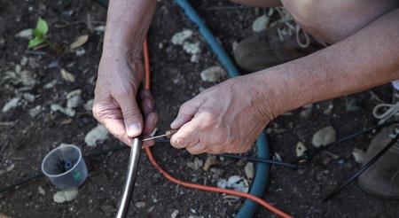 A man works on a DIY sprinkler system in his backyard.