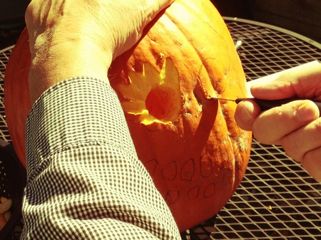 man: Man carving a Halloween pumpkin outdoors