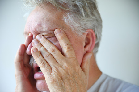 A senior man experiencing stuffy nose clogged sinuses and headache of a bad flu or cold
