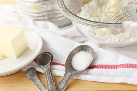 sifter: Mixing bowl with flour and butter vintage sifter measuring spoons and dish cloth Stock Photo