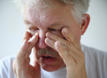 A senior man tries to relieve his stuffy nose. Stock Photo