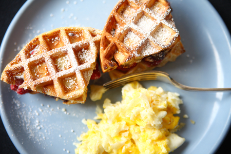Breakfast of scrambled eggs and waffles stuffed with raspberries and chocolate spread with powdered sugar sprinkled over