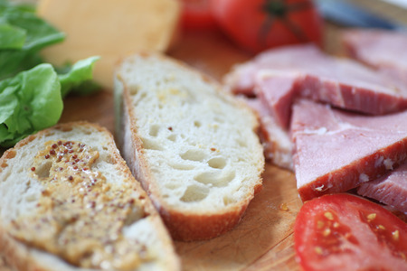 wholegrain mustard: Bread with whole-grain mustard, ham slices, cheese, lettuce and tomato, ready to make into a lunch sandwich