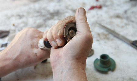 twists: A man twists the upper portion of a sprinkler head.
