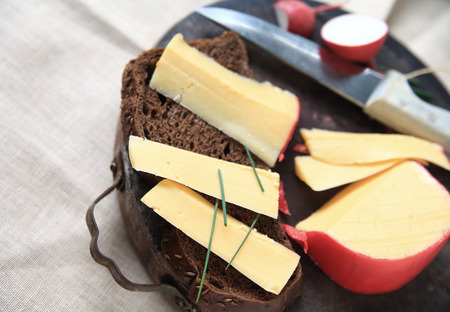 Slices of Gouda cheese with dark bread and chives on cutting board with room for text