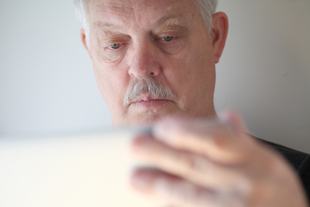 man using computer: A senior man with a hand on his laptop cover checks his screen.