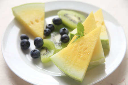 kiwi fruta: Yellow seedless watermelon with blueberries and kiwifruit on a white plate with mint