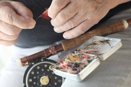 volar: Un pescador con caña de pescar con mosca y la caja de señuelos artificiales sostiene una mosca roja.
