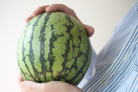 lowfat: A man holds a small watermelon.