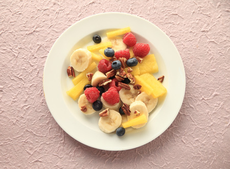 pecans: Raspberries, blueberries, yellow watermelon and bananas with chopped pecans on a white plate on a textured pale pink background