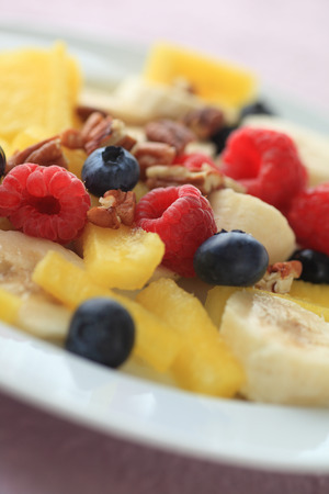 pecans: Plate of raspberries, blueberries, watermelon, bananas with chopped pecans