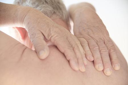 Senior man probeert de pijnlijke gebied te bereiken op zijn rug.