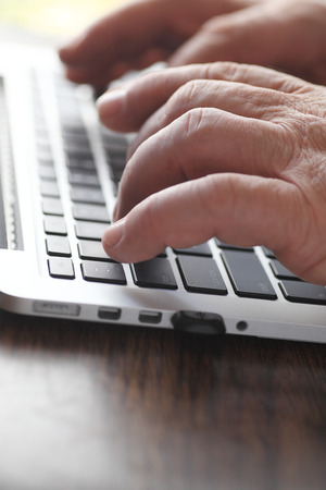 computer keyboard: Senior man hands at a laptop keyboard Stock Photo