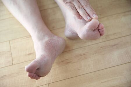 touching toes: An older man touches his toes from a sitting position on the floor.
