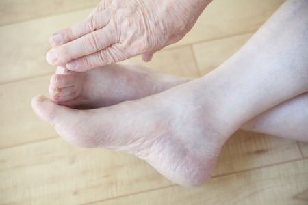 touching toes: An older man reaches to touch his toes from a sitting position.