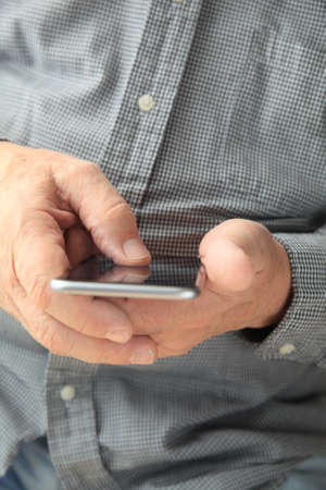 checked shirt: Man in checked shirt using his mobile device Stock Photo