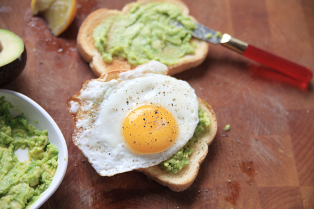 Two slices of avocado toast, one with a fried egg on top