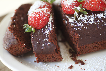 chocolate cake: Chocolate loaf cake with fresh strawberries and powdered sugar on top Stock Photo