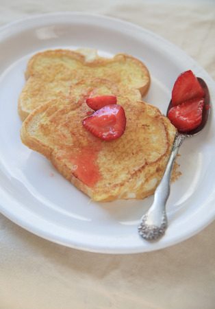 macerated: Macerated strawberries spooned over French toast on a white platter