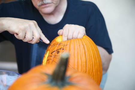 carves: Guided by his sketch, an older man carves a jack o lantern.