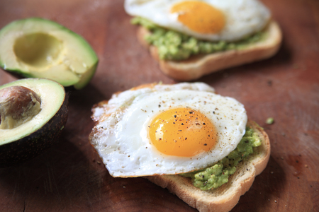 Avocado toast topped with a fried egg and black pepper Banque d'images