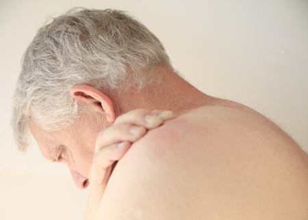 rash: Older man with an itchy rash on his back