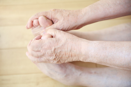 Senior man stretches, and holds his toes. Stock Photo
