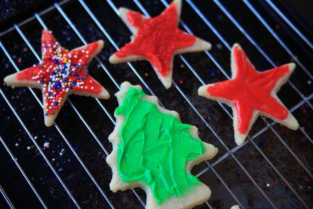saturated color: Star and tree-shaped cookies with red and green icing, one with sprinkles, cooling on a rack