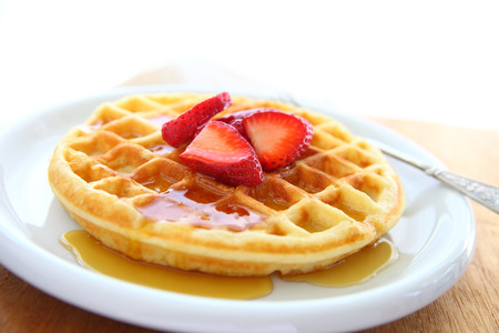 Closeup of waffle with fresh strawberries and syrup with copy space