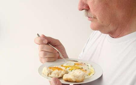 huevos estrellados: Un hombre listo para comer su desayuno de huevos fritos Foto de archivo