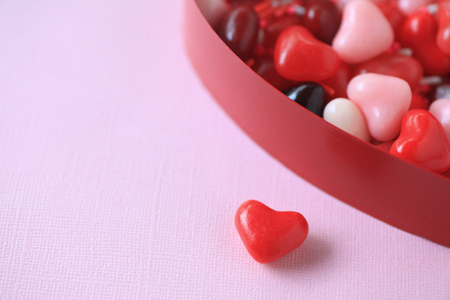 natural background: Brightly-colored Valentine candy with sprinkles in a heart box with copy space