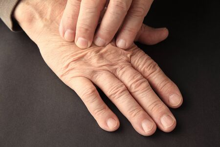 An older man has pain on his hand on a black background. Imagens