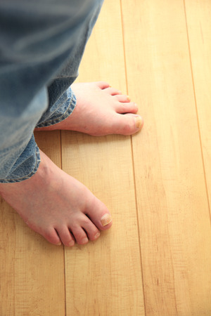bare feet: Man in jeans with bare feet on floor with copy space