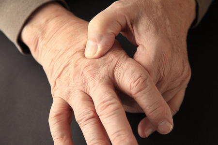 Senior man indicates where he feels pain on the back of his hand.