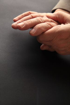 soreness: A man grips his aching hand on a dark background with copy space. Stock Photo