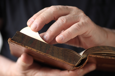 A senior man holds an antique book, and turns a page.