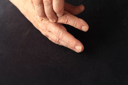 soreness: Older man with soreness near a joint on his hand Stock Photo