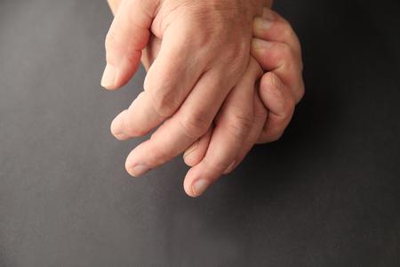soreness: Senior man holding his painful hand