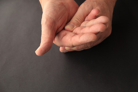 soreness: A senior man applies light pressure to the palm of his hand.