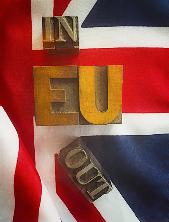 news current events: the words in and out in metal type with EU in wood type on a UK flag Stock Photo