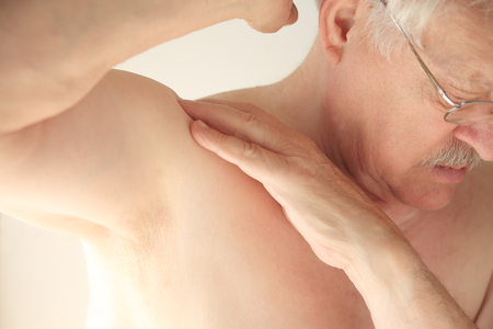 tries: An older man tries to move his shoulder without pain.