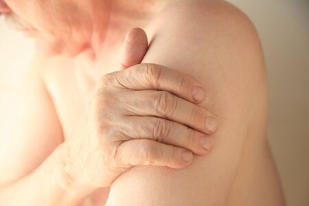 soreness: An older man with his hand on an area of soreness on his upper arm Stock Photo