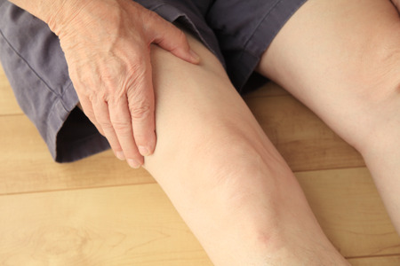 Older man sitting on the floor has a hand on his painful thigh muscle.
