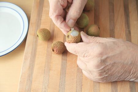 wood textures: A man begins to peel a fresh lychee on a cutting board.