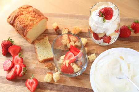 trifle: Overhead of strawberries, whipped cream and pound cake with finished miniature trifle on cutting board