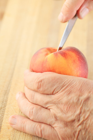 paring: A man cuts into a peach with a paring knife.