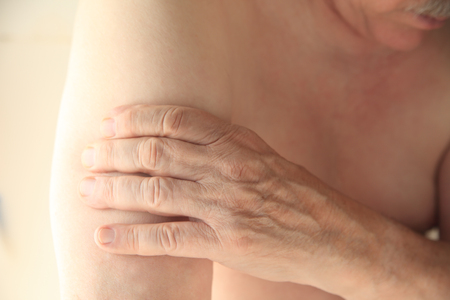 soreness: A man experiences soreness in his upper arm.