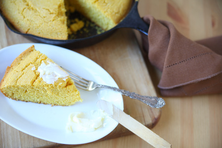 cornbread: Portion of cornbread with butter with the rest in a cast iron skillet behind