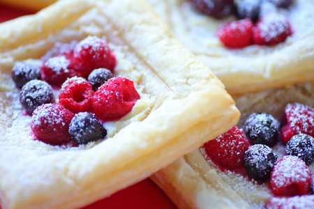 Closeup of powdered sugar-dusted pastries topped with fresh raspberries, blackberries and blueberries Stock Photo
